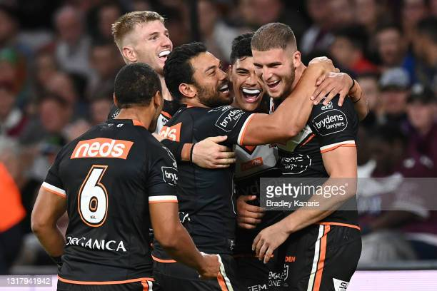 Adam Doueihi of the Tigers celebrates with team mates after scoring a try during the round 10 NRL match between the Wests Tigers and the Newcastle...