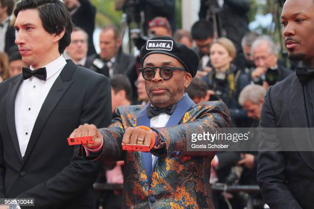 Adam Driver looks on as Corey Hawkins looks at the hands of director Spike Lee wearing knuckle rings with love and hate on them as they attends the...