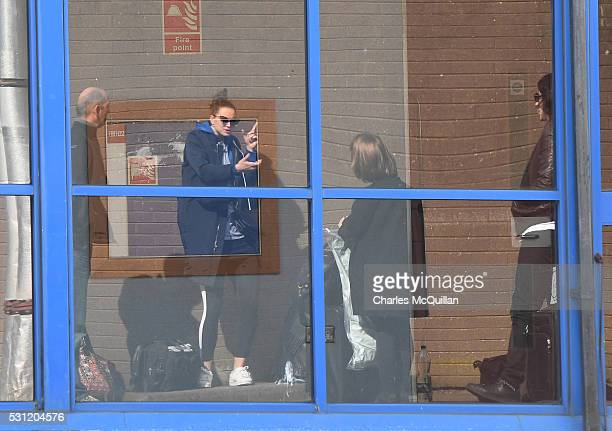 Adam Driver who plays Kylo Ren and Daisy Ridley who plays the character Rey in the Star Wars series can be seen reflected in a window as they hide...