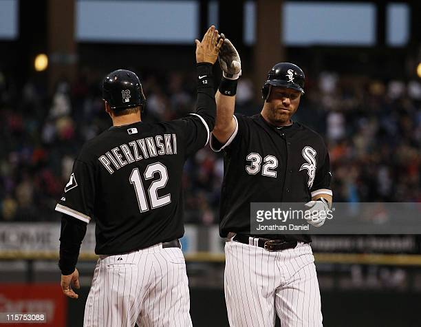 Adam Dunn of the Chicago White Sox is congratulated by teammate AJ Pierzynski after hitting a tworun home run in the 3rd inning against the Oakland...