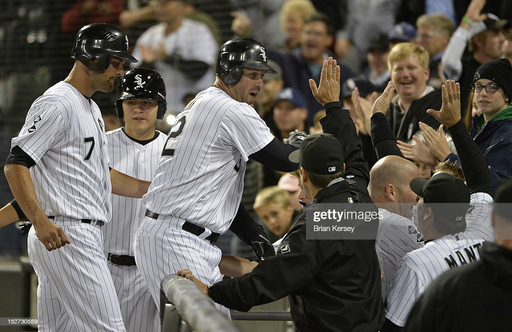 Adam Dunn #32 of the Chicago White Sox is greeted at the dugout after hitting a three-run home run scoring Jordan Danks #7 (L) and Kevin Youkilis #20 during the eighth inning against the Cleveland Indians at U.S. Cellular Field on September 24, 2012 in Chicago, Illinois. The White Sox defeated the Indians 5-4.