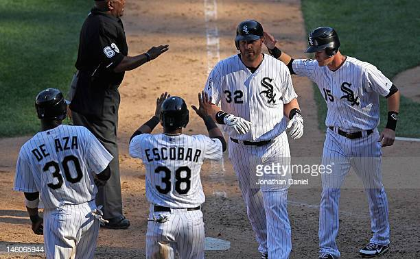 Adam Dunn of the Chicago White Sox is greeted by Alejandro De Aza Eduardo Escobar and Gordon Beckham after hitting a grand slam home run in the 8th...
