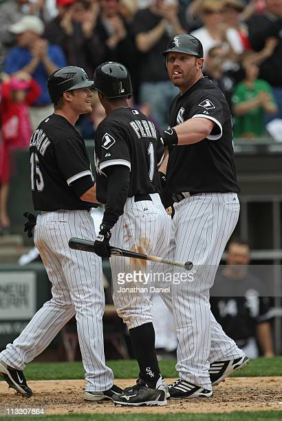 Adam Dunn of the Chicago White Sox is greeted by teammates Giordon Beckham and Juan Pierre after hitting a pinchhit tworun home run in the 8th inning...