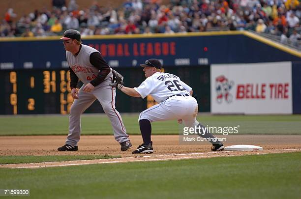 Adam Dunn of the Cincinnati Reds gets a lead off first as Chris Shelton of the Detroit Tigers holds him close on May 21 2006 at Comerica Park in...
