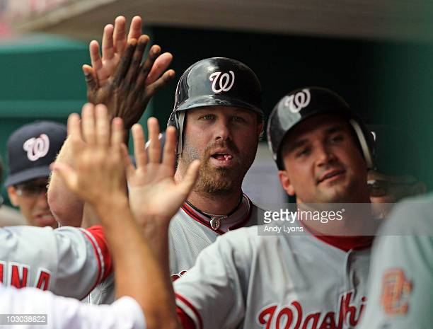Adam Dunn of the Washington Nationals is congratulated by teammates after hitting a home run during the game against the Cincinnati Reds at Great...