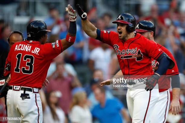 Adam Duvall of the Atlanta Braves celebrates with Ronald Acuna Jr. #13 after a two-run home run off Jack Flaherty of the St. Louis Cardinals in the...