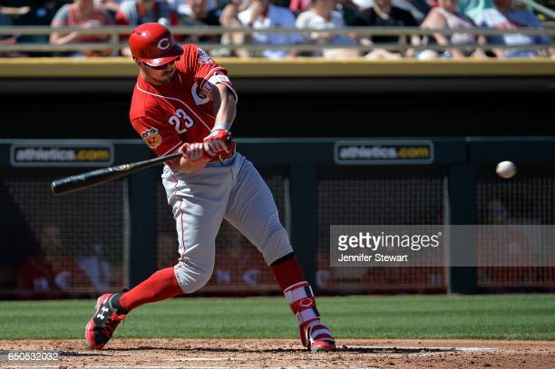 Adam Duvall of the Cincinnati Reds hits a solo home run in the second inning in the spring training game against the Oakland Athletics at HoHoKam...