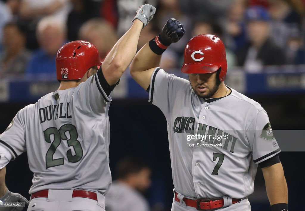 Adam Duvall #51 of the Cincinnati Reds is congratulated by Eugenio Suarez #7 after hitting a solo home run in the sixth inning during MLB game action against the Toronto Blue Jays at Rogers Centre on May 29, 2017 in Toronto, Canada.