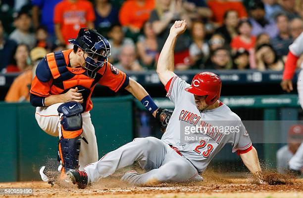 Adam Duvall of the Cincinnati Reds scores on a double by Eugenio Suarez in the eleventh inning as Jason Castro of the Houston Astros is late with the...