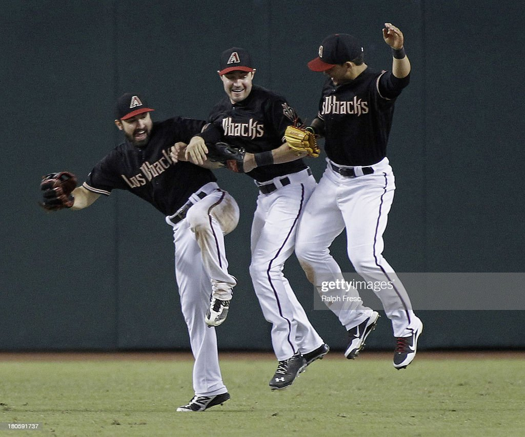 Adam Eaton #6, A.J. Pollock #11 and Gerardo Parra #8 of the Arizona Diamondbacks leap together in celebration of their 9-2 victory over the Colorado Rockies during a MLB game at Chase Field on September 14, 2013 in Phoenix, Arizona.