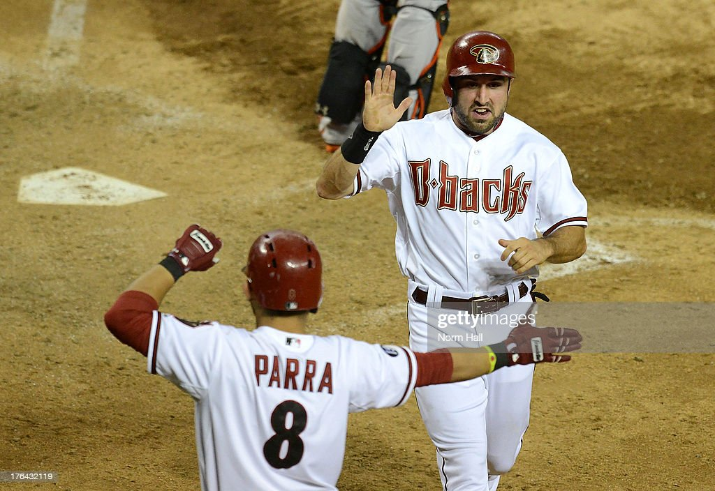 Adam Eaton #6 of the Arizona Diamondbacks is met at home plate by teammate Gerardo Parra #8 after scoring the go-ahead run in the seventh inning against the Baltimore Orioles at Chase Field on August 12, 2013 in Phoenix, Arizona.