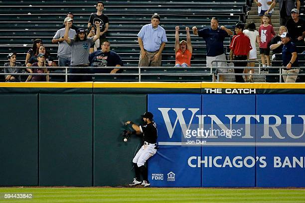 Adam Eaton of the Chicago White Sox is unable to hold on to a catch after colliding with the outfield wall du9 against the Philadelphia Phillies at...