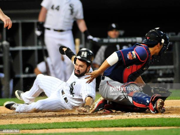 Adam Eaton of the Chicago White Sox scores as Kurt Suzuki of the Minnesota Twins makes a late tag during the seventh inning on August 2 2014 at US...