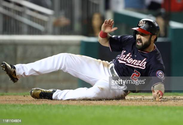 Adam Eaton of the Washington Nationals celebrates as he slides home to score on an RBI double hit by teammate Anthony Rendon in the third inning of...