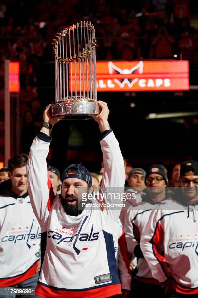 Adam Eaton of the Washington Nationals holds the Commissioner's Trophy as the Nationals are honored during a pregame ceremony to celebrate the...