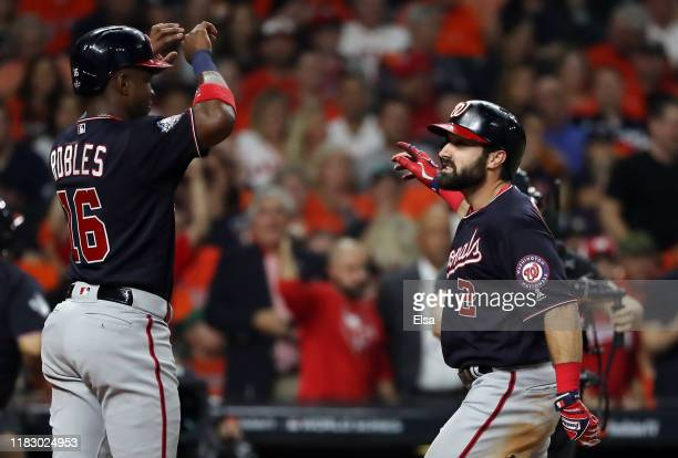 Adam Eaton of the Washington Nationals is congratulated by his teammate Victor Robles after hitting a two-run home run against the Houston Astros...