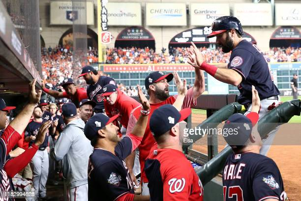 Adam Eaton of the Washington Nationals is congratulated by his teammates after scoring a run against the Houston Astros during the first inning in...