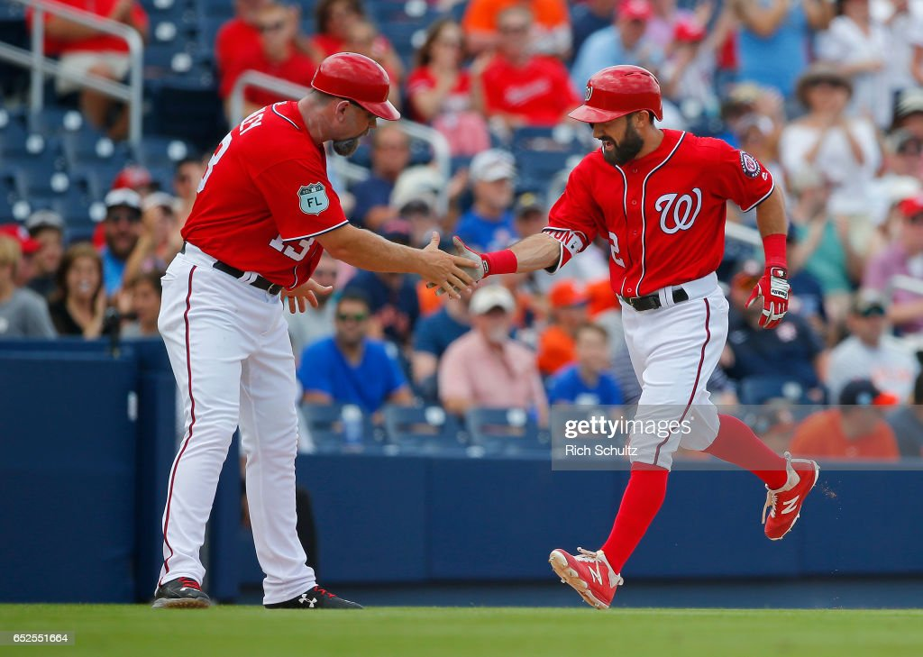 Adam Eaton #2 of the Washington Nationals is congratulated by third base coach Bobby Henley after he hit a home run during the fourth inning against the Houston Astros during a spring training baseball game on March 12, 2017 in West Palm Beach, Florida.
