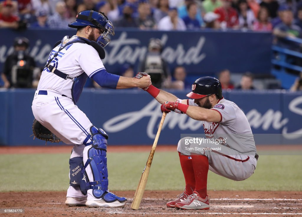 Adam Eaton #2 of the Washington Nationals is helped up by Russell Martin #55 of the Toronto Blue Jays after fouling a ball off his foot in the seventh inning during MLB game action at Rogers Centre on June 15, 2018 in Toronto, Canada.