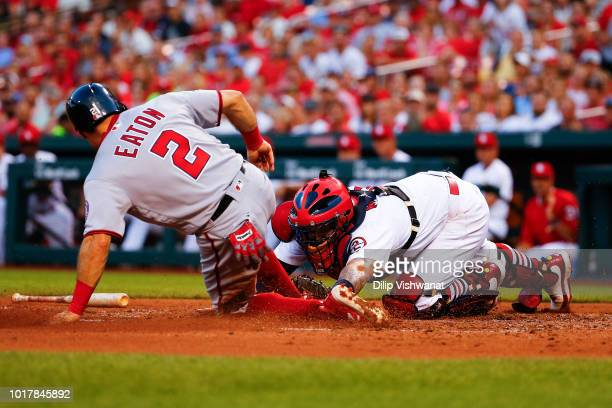 Adam Eaton of the Washington Nationals scores a run against Yadier Molina of the St Louis Cardinals in the fourth inning at Busch Stadium on August...