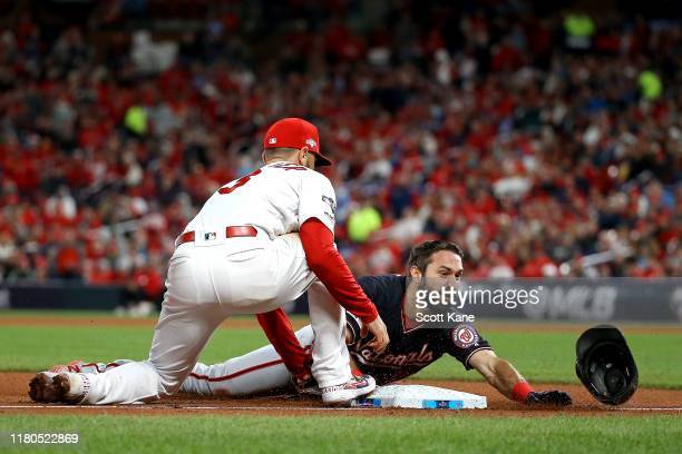 Adam Eaton of the Washington Nationals slides in safely to third base against Matt Carpenter of the St Louis Cardinals with a triple during the...