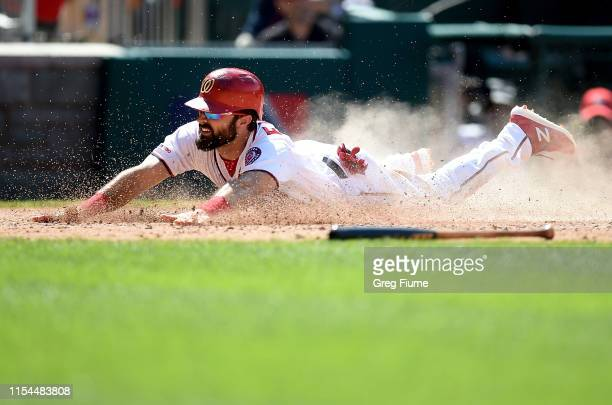 Adam Eaton of the Washington Nationals slides into home plate and scores in the eighth inning against the Kansas City Royals at Nationals Park on...