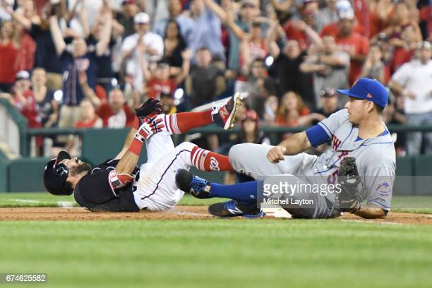 Adam Eaton of the Washington Nationals trips on base over TJ Rivera of the New York Mets in the ninth inning pitches during a baseball game at...