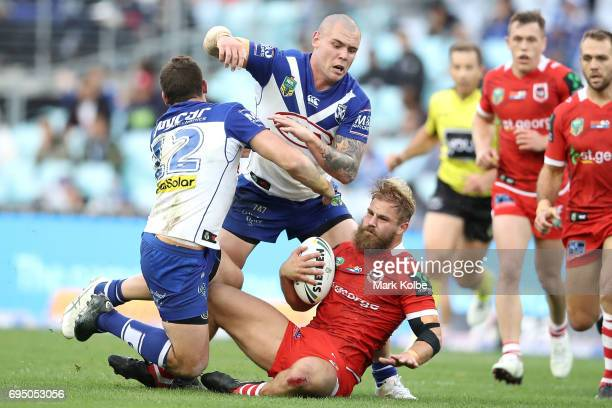 Adam Elliott and David Klemmer of the Bulldogs tackle Jack de Belin of the Dragons during the round 14 NRL match between the Canterbury Bulldogs and...