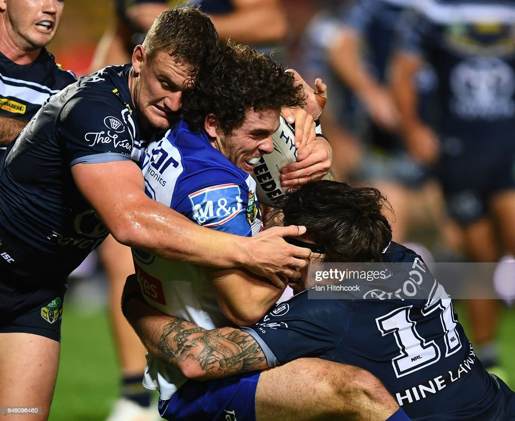 Adam Elliott of the Bulldogs is tackled by Coen Hess and Ethan Lowe of the Cowboys during the round six NRL match between the North Queensland Cowboys and the Canterbury Bulldogs at 1300SMILES Stadium on April 14, 2018 in Townsville, Australia.