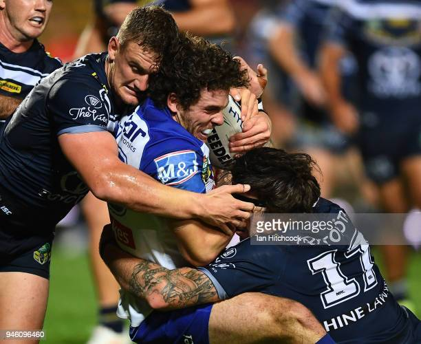 Adam Elliott of the Bulldogs is tackled by Coen Hess and Ethan Lowe of the Cowboys during the round six NRL match between the North Queensland...