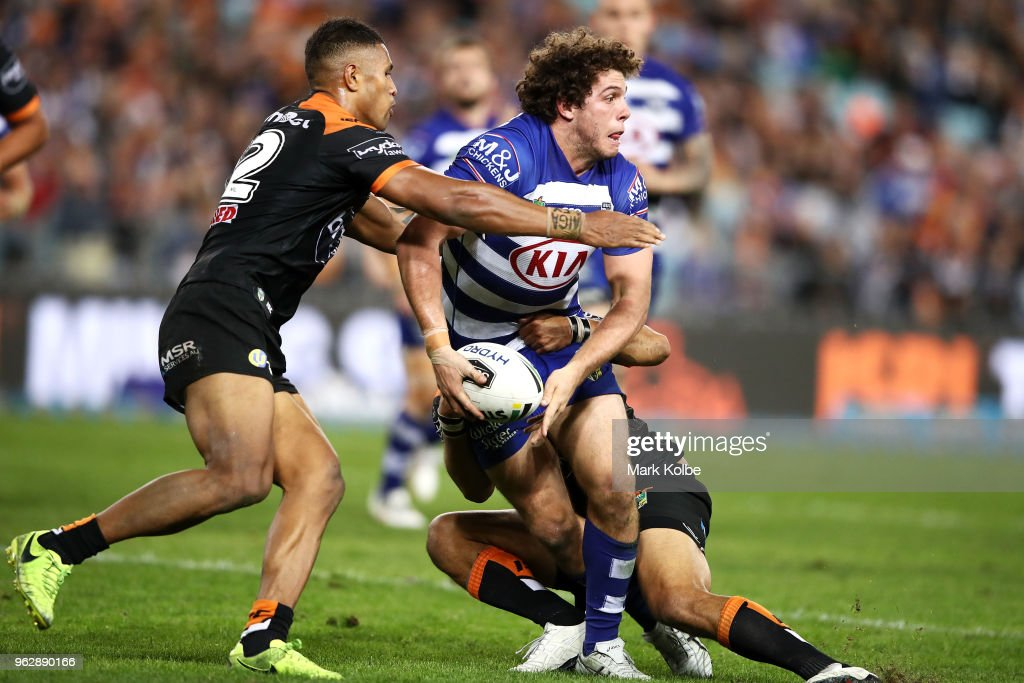 Adam Elliott of the Bulldogs looks to pass as he is tackled during the round 12 NRL match between the Wests Tigers and the Canterbury Bulldogs at ANZ Stadium on May 27, 2018 in Sydney, Australia.