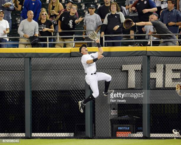Adam Engel the Chicago White Sox leaps over the wall to catch the ball and take away a home run on a ball hit by Brian McCann of the Houston Astros...