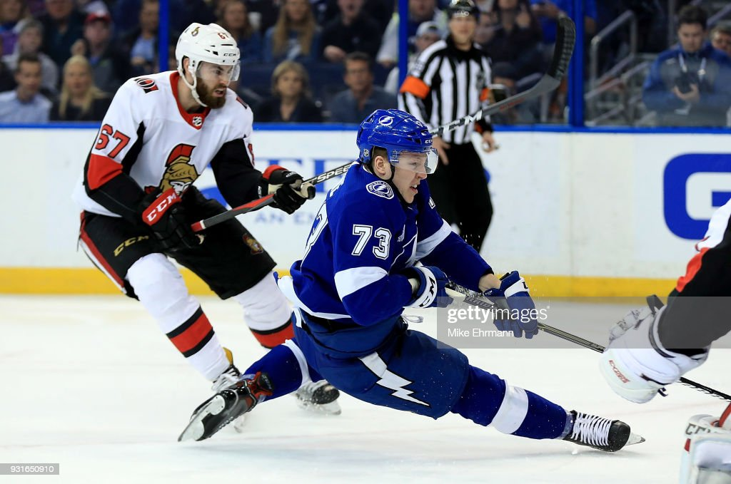 Adam Erne #73 of the Tampa Bay Lightning and Ben Harpur #67 of the Ottawa Senators fight for the puck during a game at Amalie Arena on March 13, 2018 in Tampa, Florida.