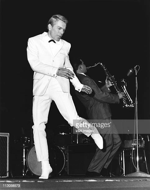 Adam Faith performs on stage wearing white suit at NME Poll Winners' Concert Wembley Empire Pool 20 February 1960