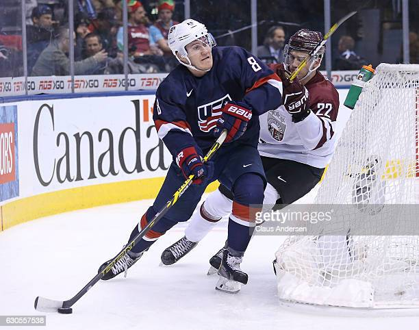 Adam Fox of Team USA skates away from a checking Filips Buncis of Team Latvia during a 2017 IIHF World Junior Hockey Championship game at the Air...