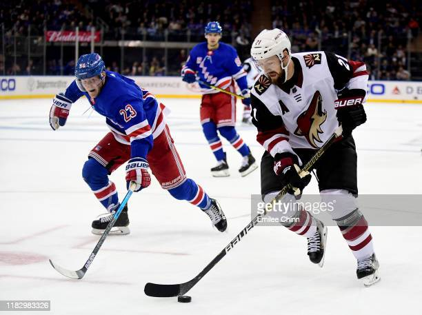 Adam Fox of the New York Rangers chases Derek Stepan of the Arizona Coyotes as he controls the puck during their game at Madison Square Garden on...