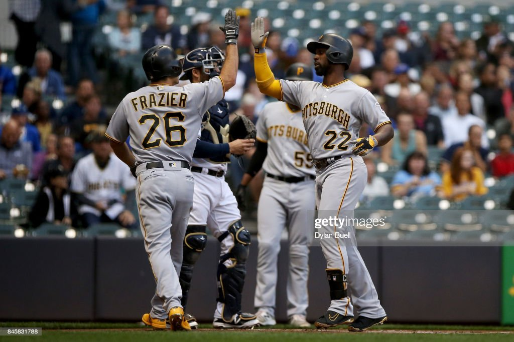 Adam Frazier #26 and Andrew McCutchen #22 of the Pittsburgh Pirates celebrate after McCutchen hit a home run in the first inning against the Milwaukee Brewers at Miller Park on September 11, 2017 in Milwaukee, Wisconsin.