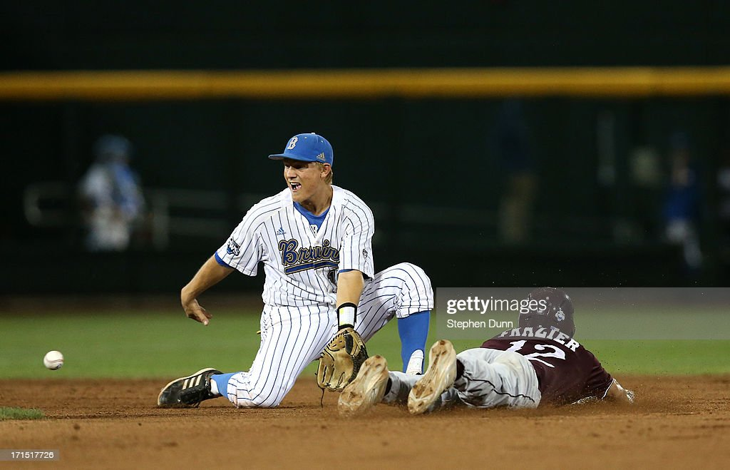 Adam Frazier #12 of the Mississippi State Bulldogs slides into second with a stolen base ahead of the throw to shortstop Pat Valaika #10 of the UCLA Bruins in the eighth inning during game two of the College World Series Finals on June 25, 2013 at TD Ameritrade Park in Omaha, Nebraska. UCLA won 8-0 to take the series two games to none and win the College World Series Championship.