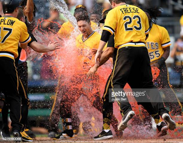 Adam Frazier of the Pittsburgh Pirates is dumped with powerade by teammates as he crosses home plate after hitting a walk off home run to give the...