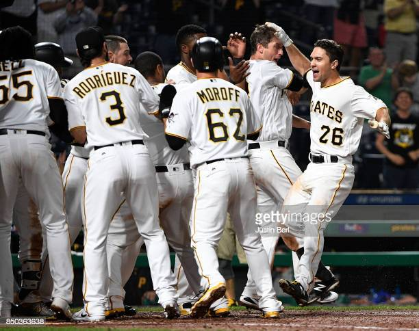 Adam Frazier of the Pittsburgh Pirates is greeted by teammates at home plate after hitting a walk off two run home run to right field in the ninth...