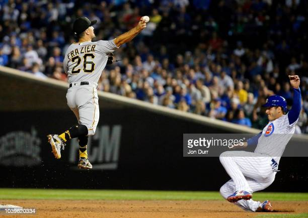 Adam Frazier of the Pittsburgh Pirates jumps and throws to first base after forcing out Anthony Rizzo of the Chicago Cubs to complete a double play...