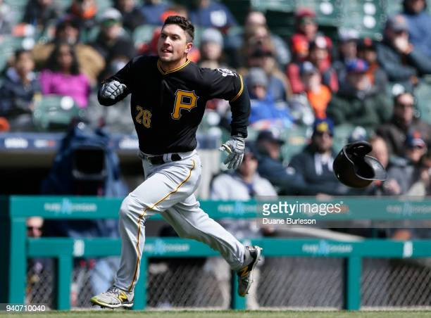 Adam Frazier of the Pittsburgh Pirates loses his helmet as he rounds third base to score against the Detroit Tigers from first base on a double by...
