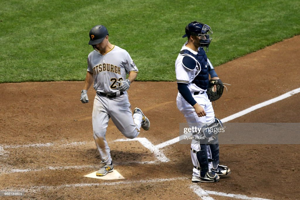 Adam Frazier #26 of the Pittsburgh Pirates scores a run past Manny Pina #9 of the Milwaukee Brewers in the sixth inning at Miller Park on May 5, 2018 in Milwaukee, Wisconsin.