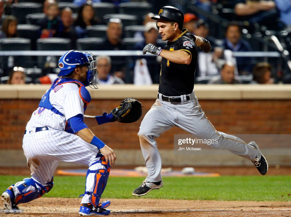 Adam Frazier #26 of the Pittsburgh Pirates scores a sixth inning run ahead of the throw to Travis d'Arnaud #18 of the New York Mets at Citi Field on June 2, 2017 in the Flushing neighborhood of the Queens borough of New York City.