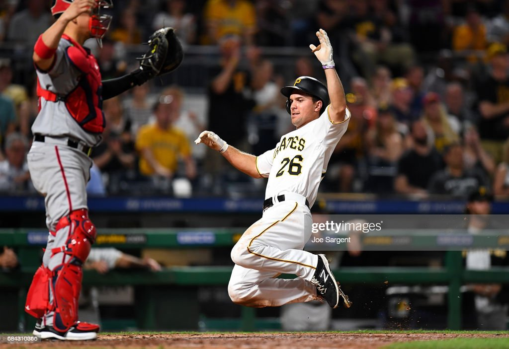 Adam Frazier #26 of the Pittsburgh Pirates slides safely into home plate during the seventh inning against the Washington Nationals at PNC Park on May 17, 2017 in Pittsburgh, Pennsylvania.