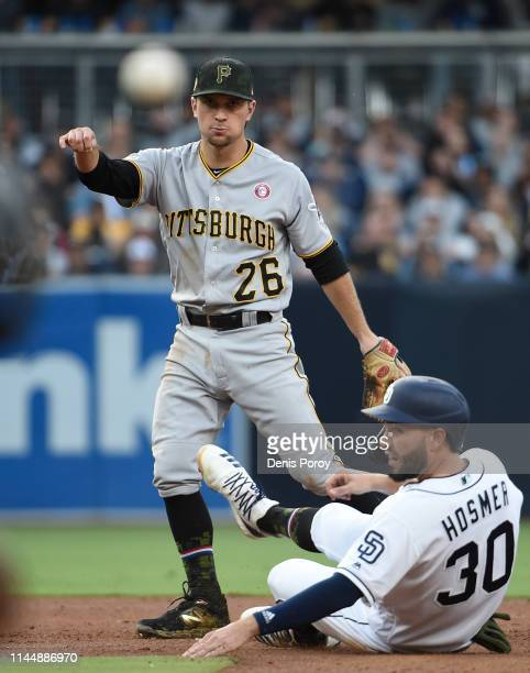 Adam Frazier of the Pittsburgh Pirates throws over Eric Hosmer of the San Diego Padres as he turns a double play during the third inning of a...