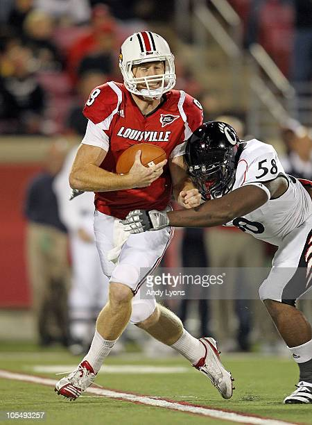 Adam Froman of the Louisville Cardinals is sacked by Brandon Mills of the Cincinnati Bearcats during the game at Papa John's Cardinal Stadium on...