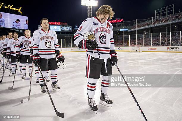 Adam Gaudette of Northeastern University looks down during the National Anthem before a Frozen Fenway game against University of New Hampshire at...