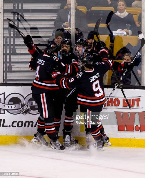 Adam Gaudette of the Northeastern Huskies celebrates after scoring a goal against the Harvard Crimson with teammates Zach AstonReese Jeremy Davies...