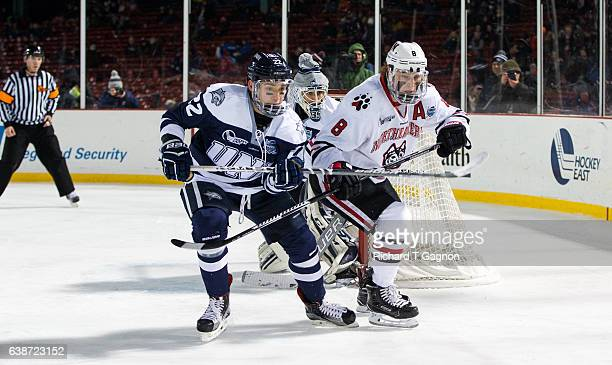 Adam Gaudette of the Northeastern Huskies fights for position against Tanner Pond of the New Hampshire Wildcats during NCAA hockey at Fenway Park...